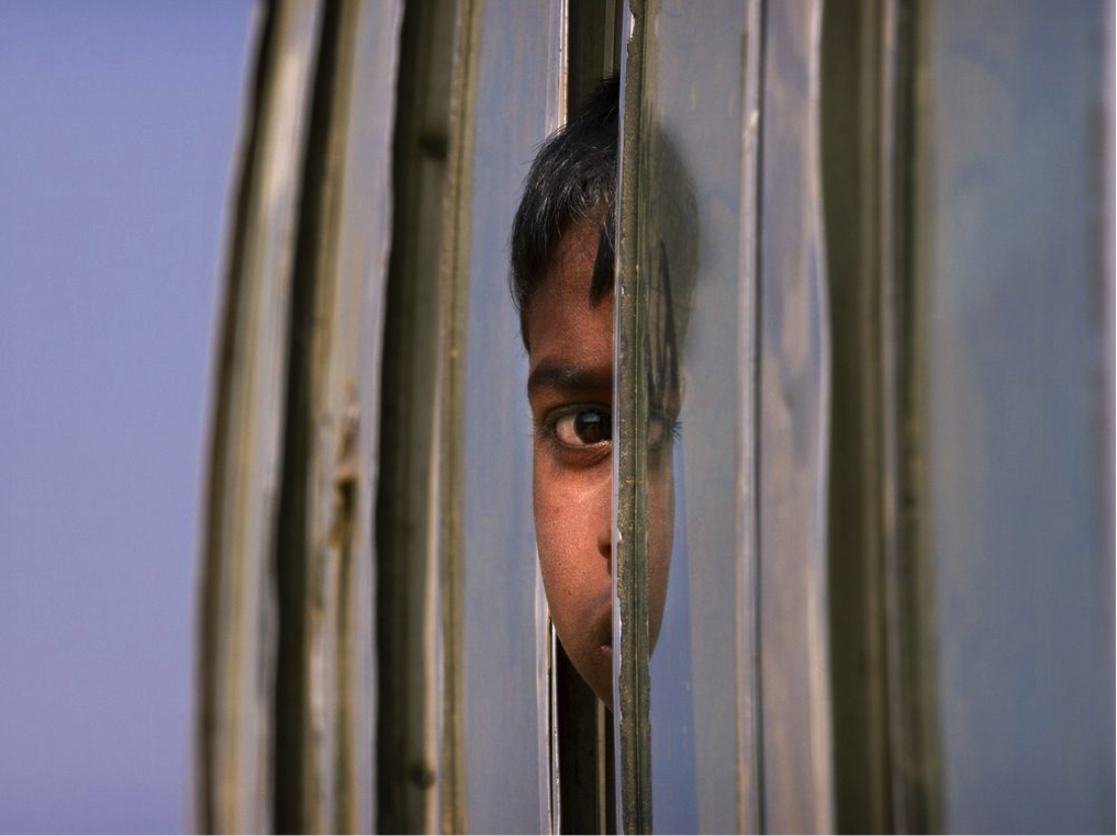 A Rohingya refugee boy who is among those being relocated from a camp near the Bangladesh-Myanmar border looks out from the window of a bus as it is brought to the Balukhali refugee camp, 50 kilometres from, Cox's Bazar, Bangladesh/ (Courtesy Manish Swarup/AP)
