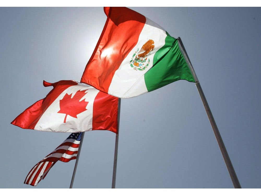 The flags of Canada, US, and Mexico fly at the last trilateral NAFTA renegotiation meeting (Image courtesy of Judi Bottoni/Associated Press)