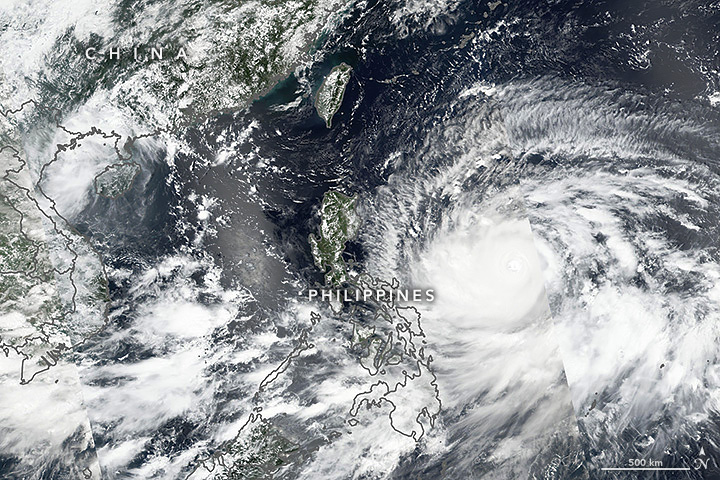 Super Typhoon Mangkhut in its most recent satellite photo approaching the Philippines, the southern coast of China, and northern Vietnam. (Image courtesy NASA Earth Observatory/Lauren Dauphin)