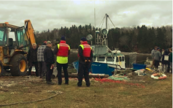 Crews work to pull the Charlene A. out of the water after it capsized off the coast of Hackett's Cove shortly after the beginning of Dumping Day. Courtesy Elizabeth McSheffrey and Global News
