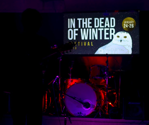 T.Thomason stands a sillouette infront a screen displaying In the Dead of Winter's logo at the Mayflower Curling Club on January 25, 2019. (Photo: Alec Martin)